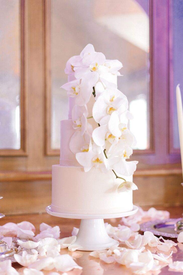 The couple's classic cake was finished with buttercream frosting and a single cascade of white orchids.