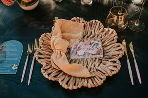 Place Setting With Rattan Charger and Orange Napkin