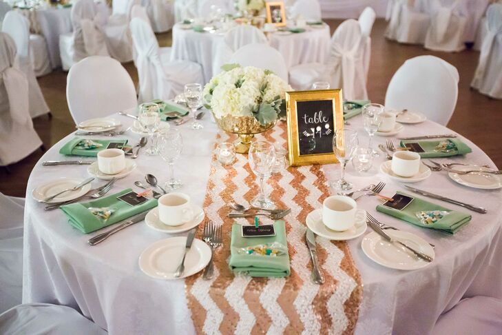 To keep the decor feeling fun and festive, the couple dressed the tables with shimmery chevron table runners and added a few gilded accents in the form of vases and frames. The gold and mint together really made the tabletops pop, while introducing an element of glamour and elegance to the the Union Steelworkers Hall in Sudbury, Ontario.