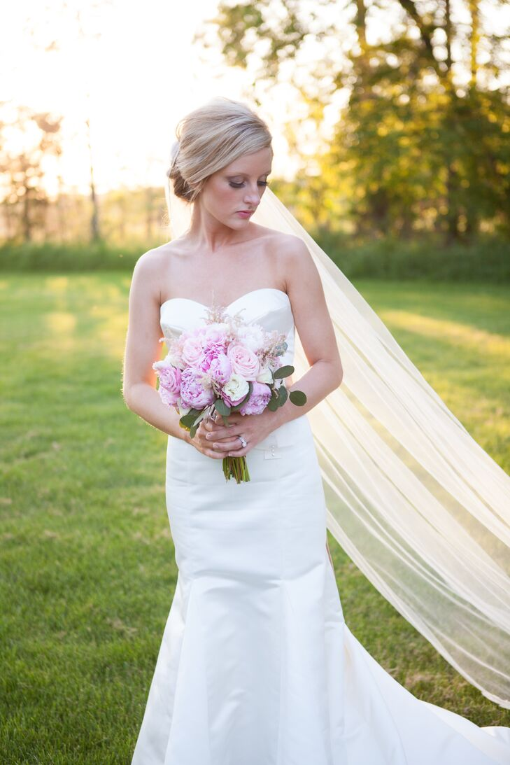 """The bride chose a classic, white, satin gown with a sweetheart neckline by Watters. A vintage Mikimoto pearl necklace that once belonged to her grandmother completed the look. """"I decided on this specific dress because not only did I love the look, but I loved the way I felt in it,"""" Erin explains."""