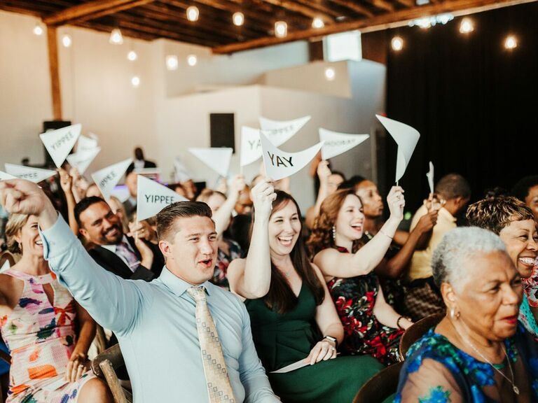 Guests waving flags in cocktail wedding attire during ceremony