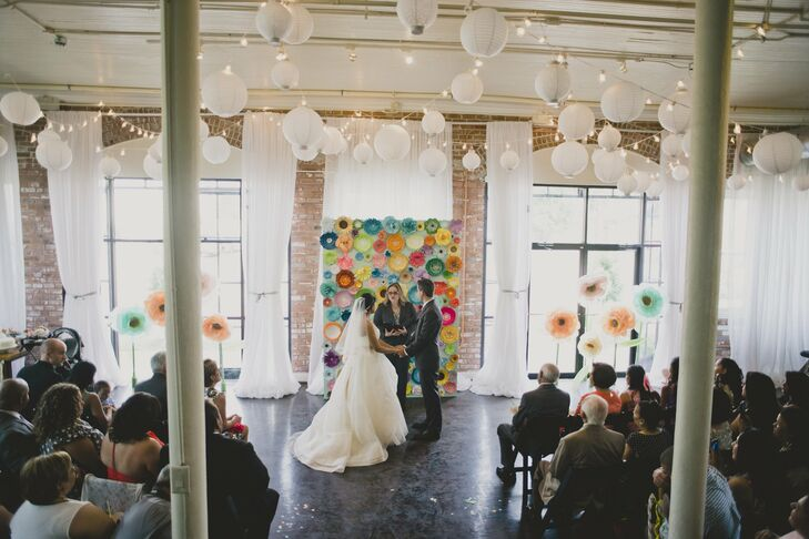 The afternoon ceremony took place downstairs in the firehouse in front of bright windows and a flower-wall backdrop. I spent two months making paper flowers while my dad and Mike constructed the wall, Kristy says.