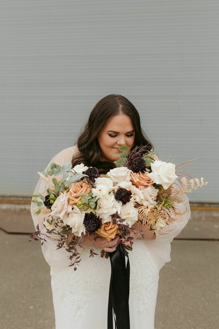 Bride holding bouquet with scabiosa and roses
