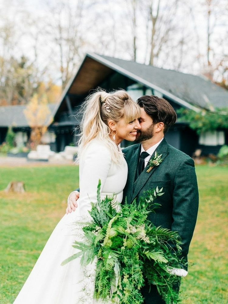 Couple embracing and holding greenery bouquet