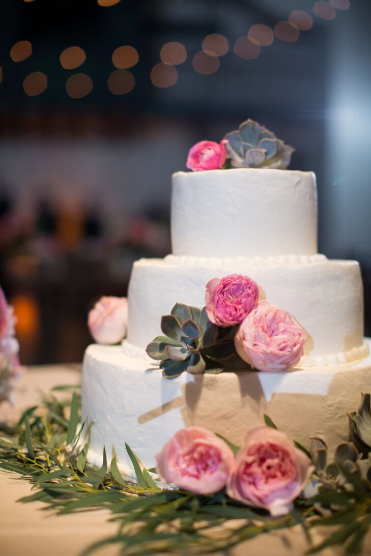 The couple's three-tier vanilla and caramel-filing wedding cake was topped with succulents and pink blooms.
