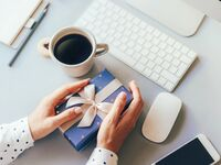 Woman holding gift at office desk wrapped in blue gift wrap with a ribbon