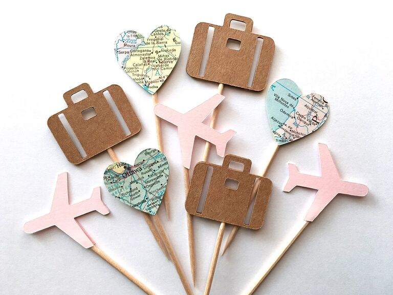 Paper cupcake toppers in pink airplane, brown luggage and heart cut out of map