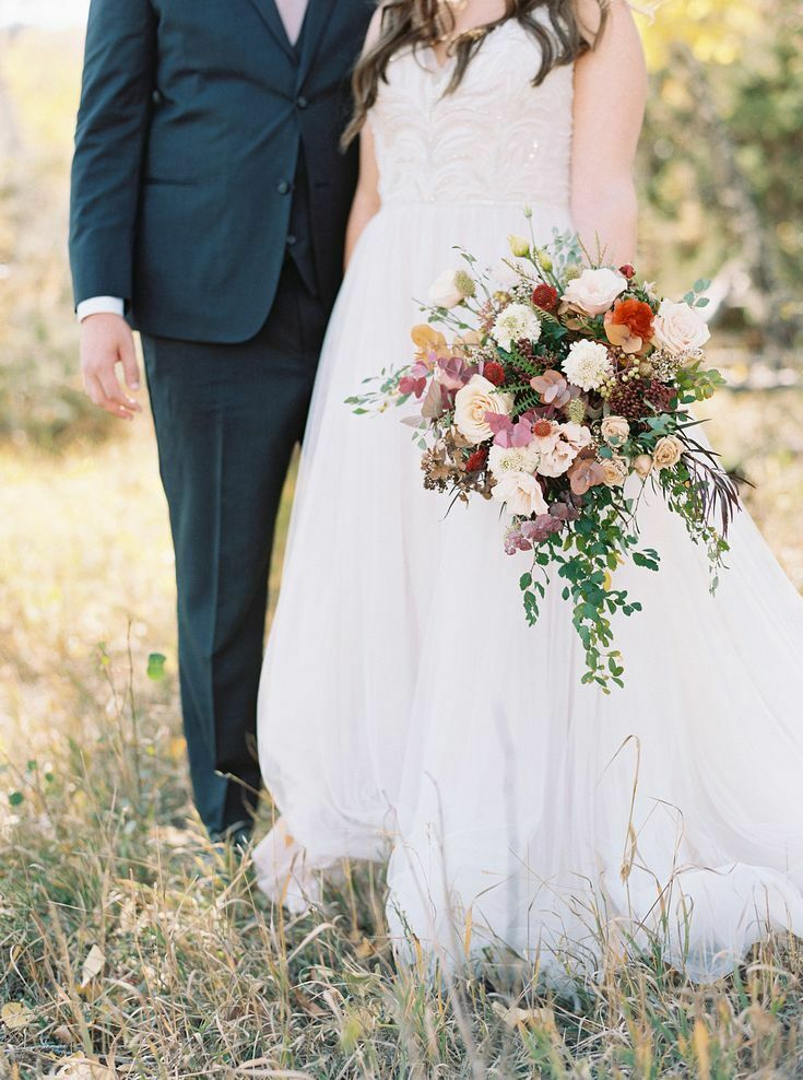 Bride standing by groom and holding bouquet by her side