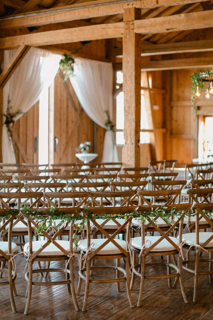 White draping, greenery and floral arrangements decorated the ceremony site, pulling double duty as reception decor after the cocktail hour, at Devil's Thumb Ranch Resort & Spa in Tabernash, Colorado.