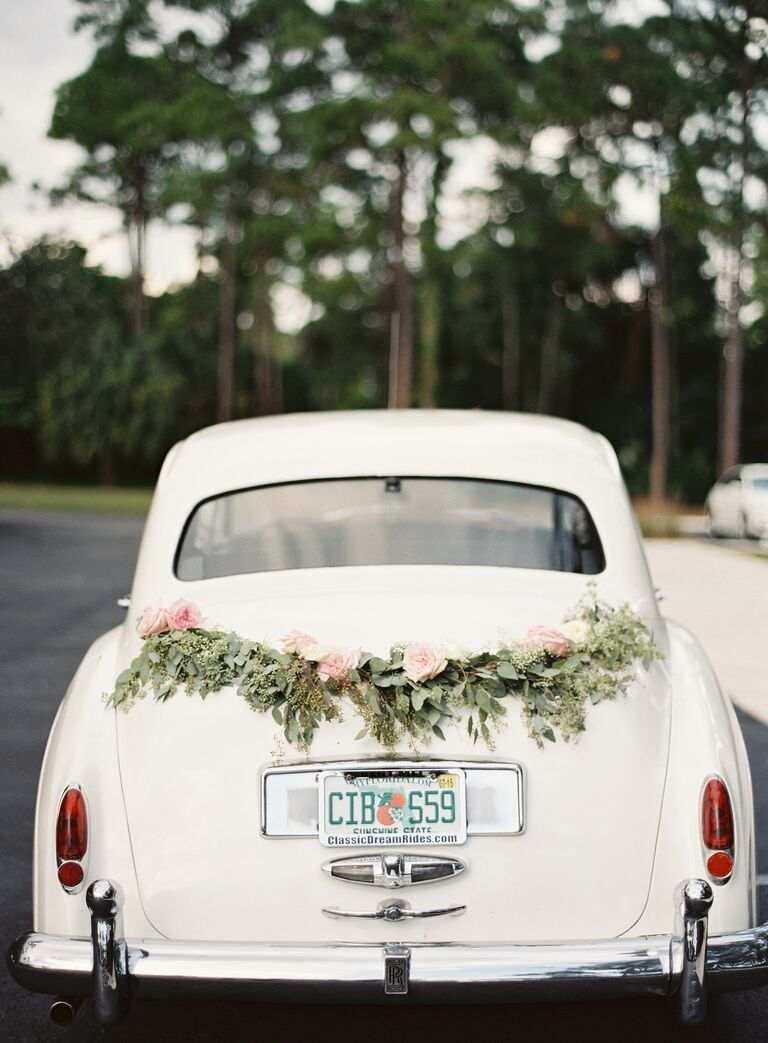 White exit car with green garland and roses