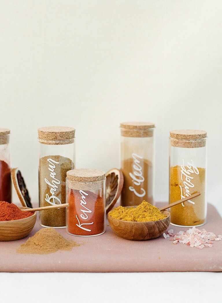 unique wedding escort cards jars of orange and yellow spices with names written in white calligraphy