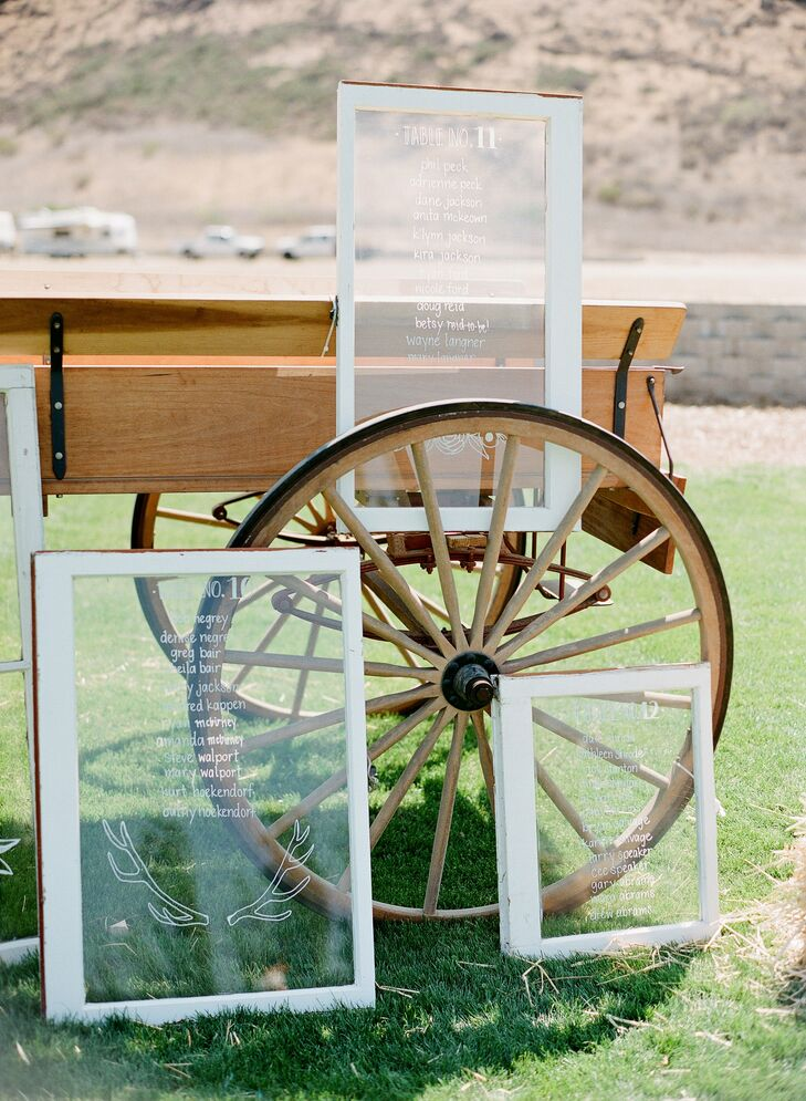 The seating assignments were written on the panes of vintage windows and displayed on a chuck wagon to go with the rustic country vibe of the day.