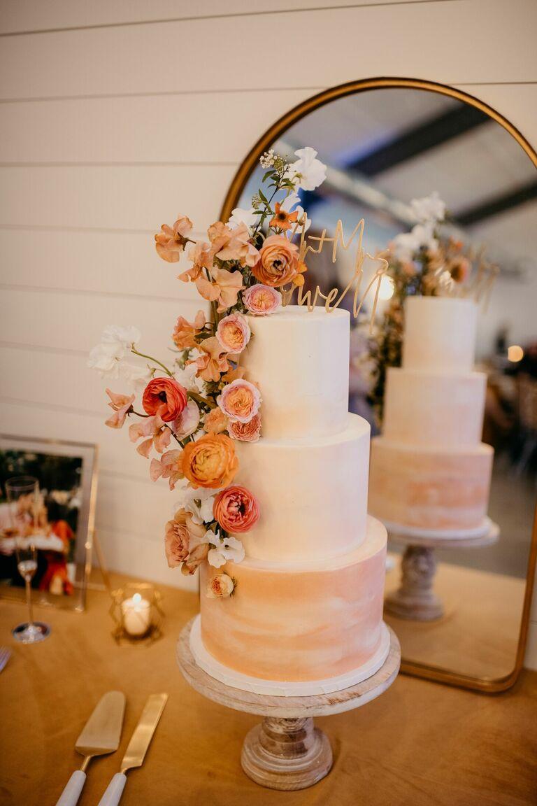Three-tier orange ombre wedding cake with orange flowers