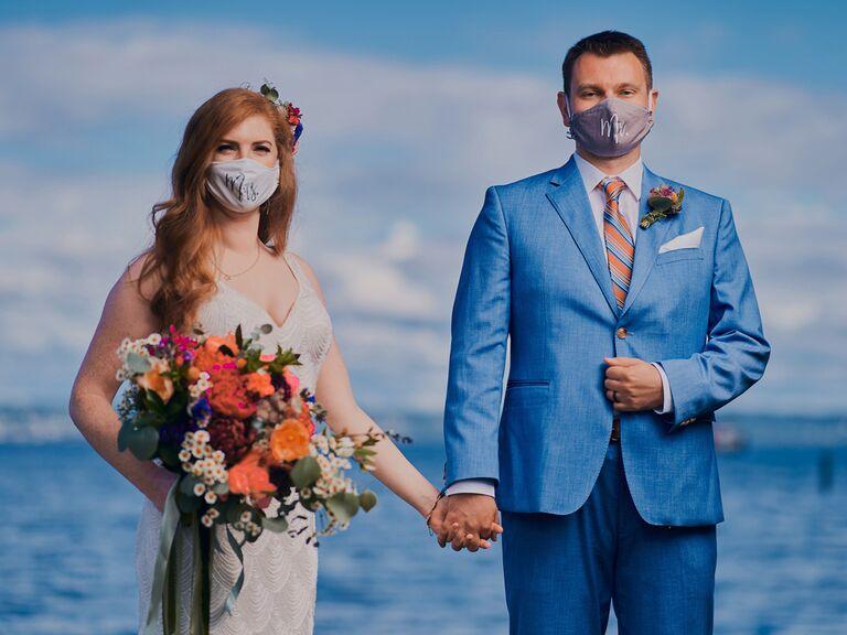 Bride and groom wearing wedding masks