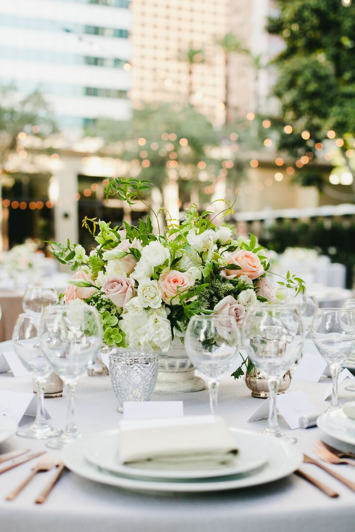 Guests sat in the Cafe Pinot garden at round white linen-topped tabled decorated with rose gold flatware and flowers set in vintage porcelain vases.