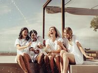 Bride and bridesmaids with champagne at bachelorette party