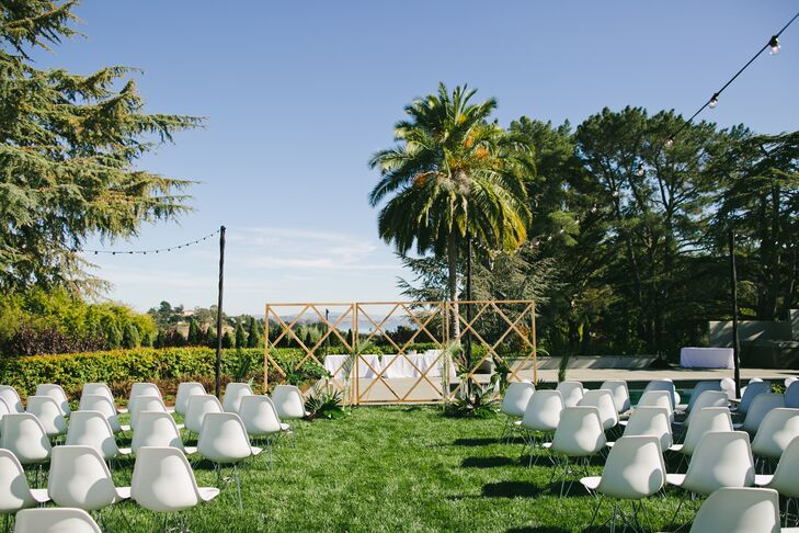 """Modern white Eames-style chairs were set up for the backyard ceremony—they doubled as chairs for the reception dinner—and neutral stone vases held pale yellow king proteas and lots of greenery. """"Scott's parents' house had such a beautiful backdrop that we didn't need to accessorize very much."""""""