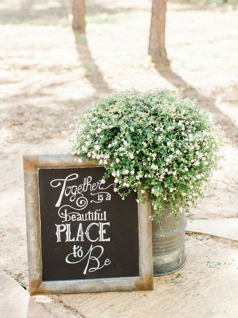 Rustic wedding chalkboard sign decoration next to potted baby's breath