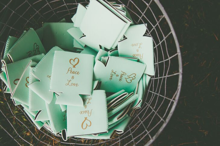 """Koozies in the same sage color as the wedding party were engraved with """"Peace & Love."""""""
