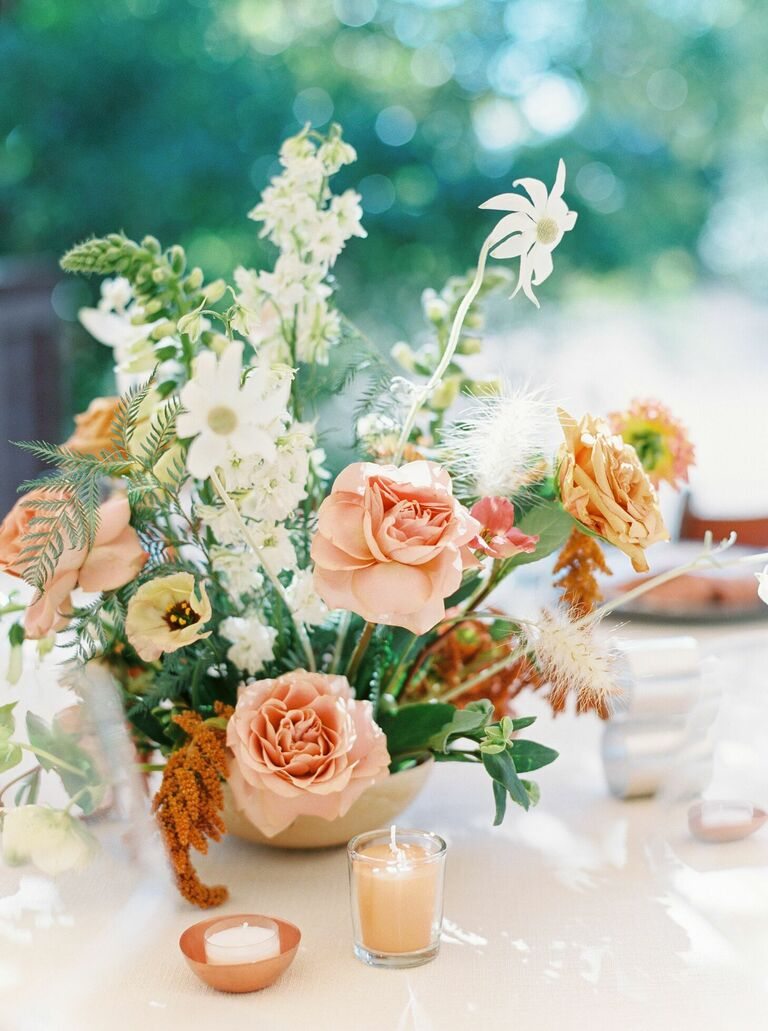 Loose floral centerpiece with roses and daisies