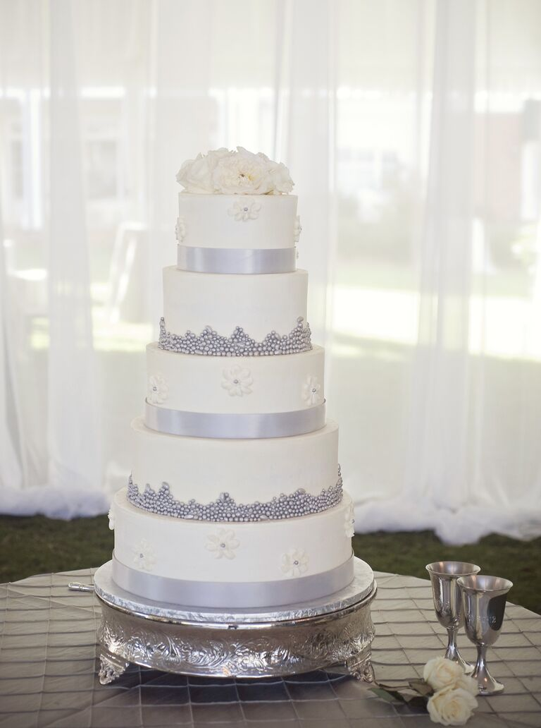 Silver and white wedding cake with flower topper
