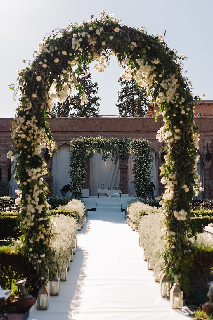 A floral archway and altar were constructed to add drama to the intimate space, and the aisle was lined with hedgerows of baby's breath punctuated with silver lanterns.