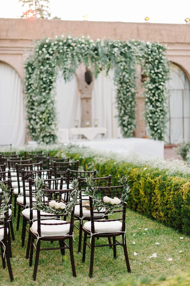 Moroccan lanterns lined the aisle, which was covered in a white capret to match the linen chair cushions.
