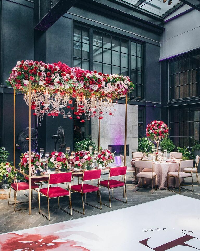 Glam red-and-pink reception with crystal chandeliers and rose decorations