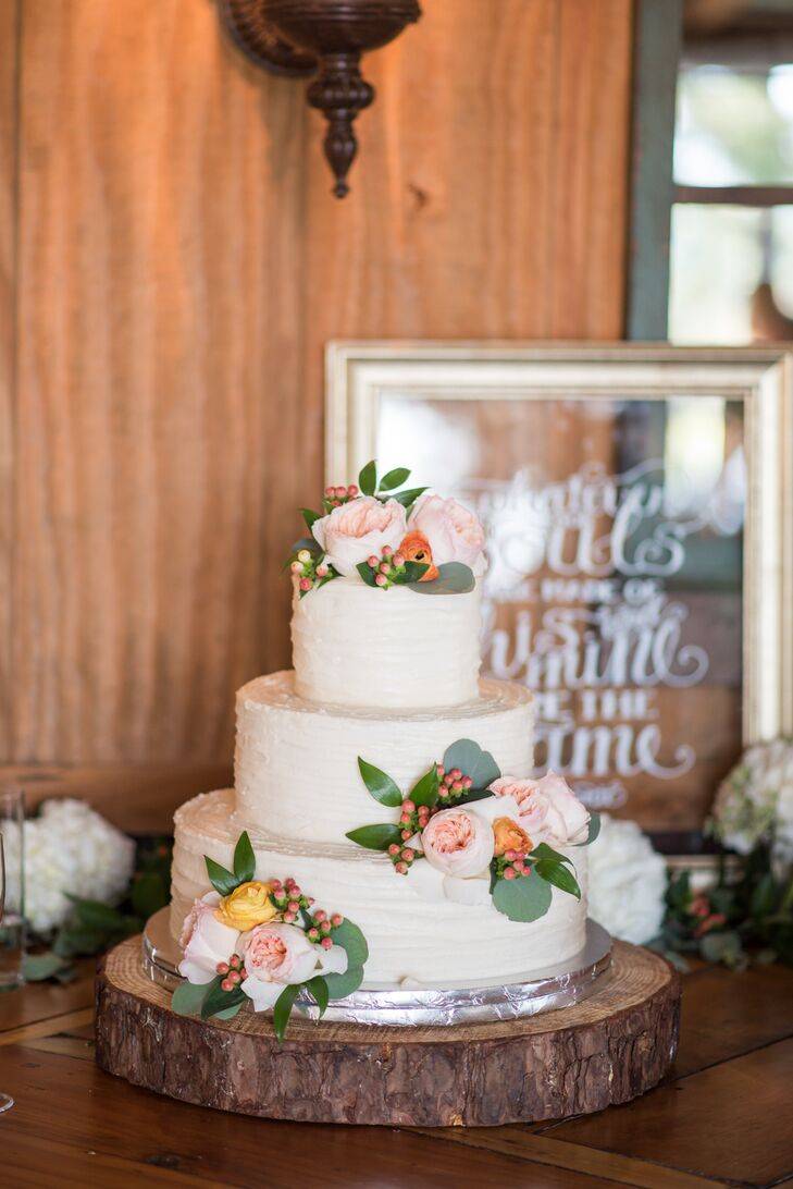 """Morgan and Park's three-tier cake with cinnamon, chocolate and vanilla flavoring was iced in vanilla buttercream frosting and decorated with flowers that complemented the bouquets. Next to the cake, a hand-painted sign read, """"Whatever our souls are made of, his and mine are the same."""""""