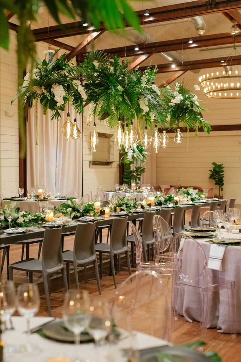Tropical wedding reception with greenery chandelier
