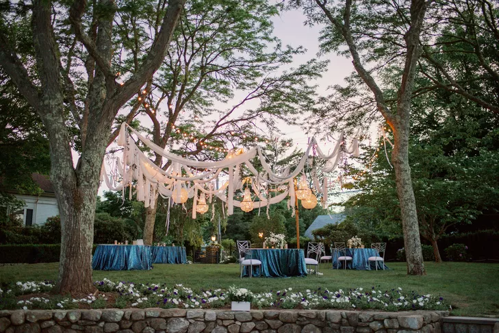 Outdoor wedding reception with fabric draping among the trees
