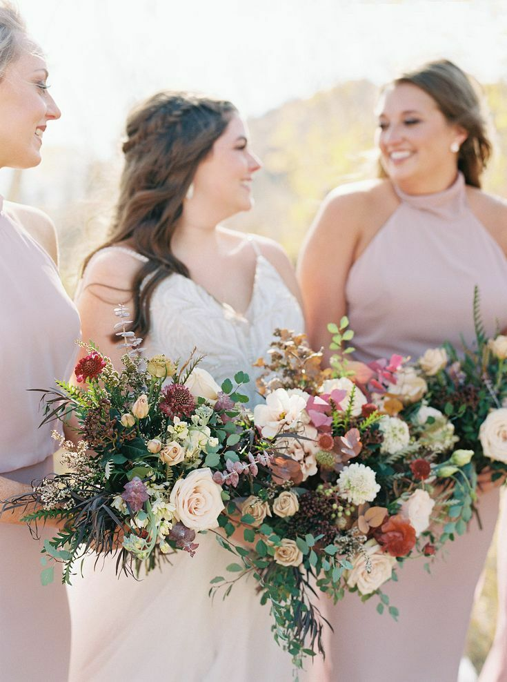 bride and bridesmaids posing together and holding bouquets