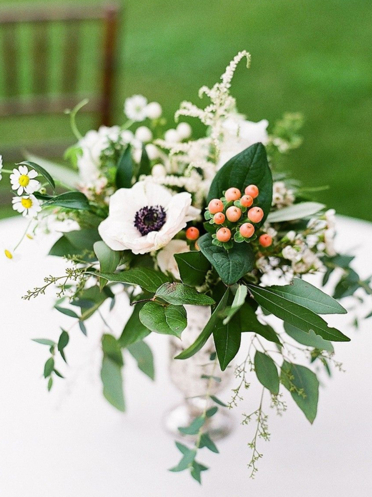 Centerpiece with anemone, hypericum, greenery and astilbe