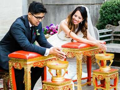 Couple smiling at each other during traditional Thai water blessing ceremony