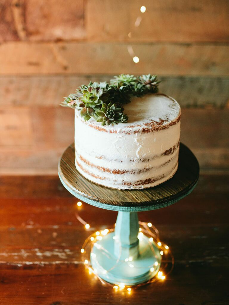 Single-tier semi-naked rustic cutting cake with fairy lights twisted around cake stand