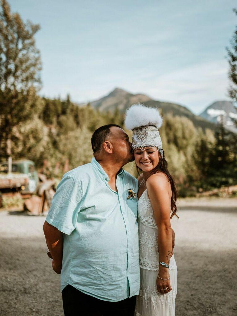 Father of the bride kissing Yupik Eskimo bride on the cheek