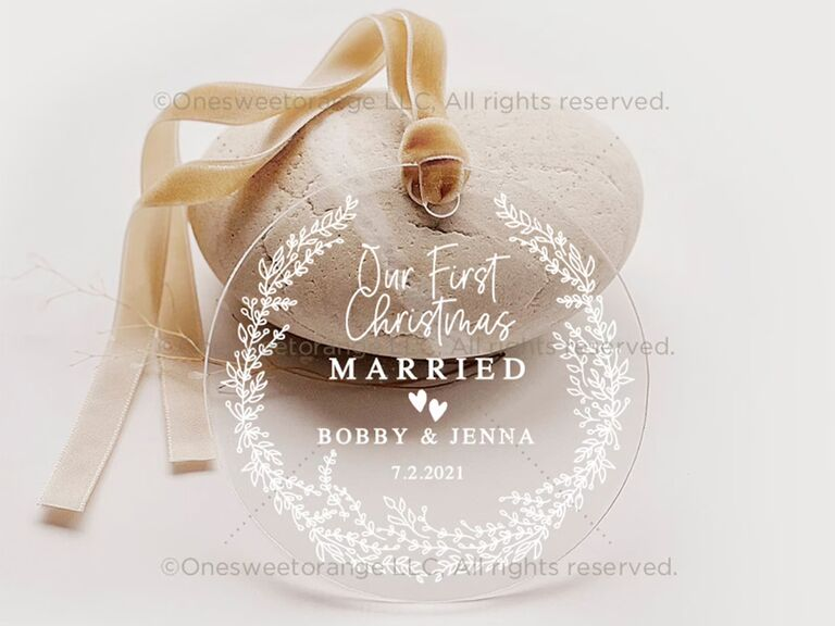 Circle clear acrylic ornament bordered with white sprigs and 'Our first Christmas Married' in minimalist white type
