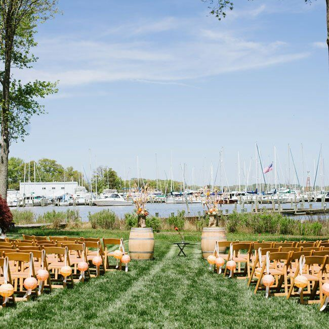 The ceremony was held outside right next to the water. Two wine barrels, topped with rustic floral arrangements, stood on either side of the altar area.