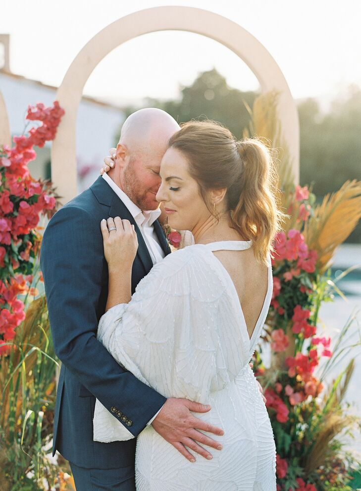 Bride and Groom Share a Hug in Front of Wedding Arch and Bougainvillea