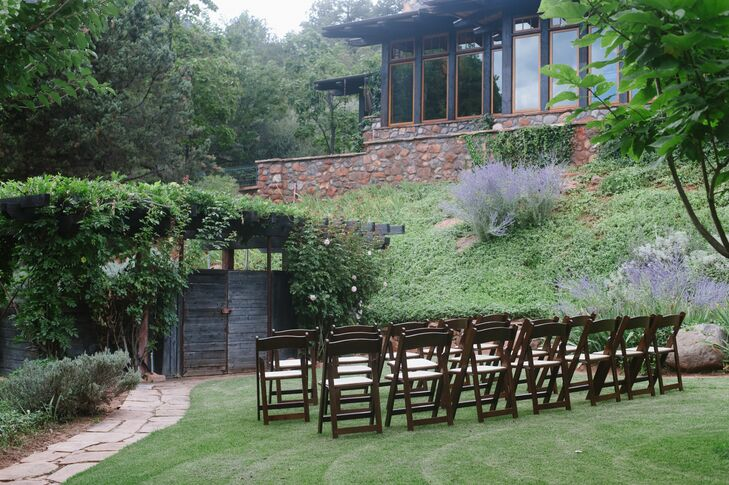 The ceremony took place by an ivy-draped wooden wedding arch on a lower-tiered lawn of the Segner Country Ranch Estate at sunset.