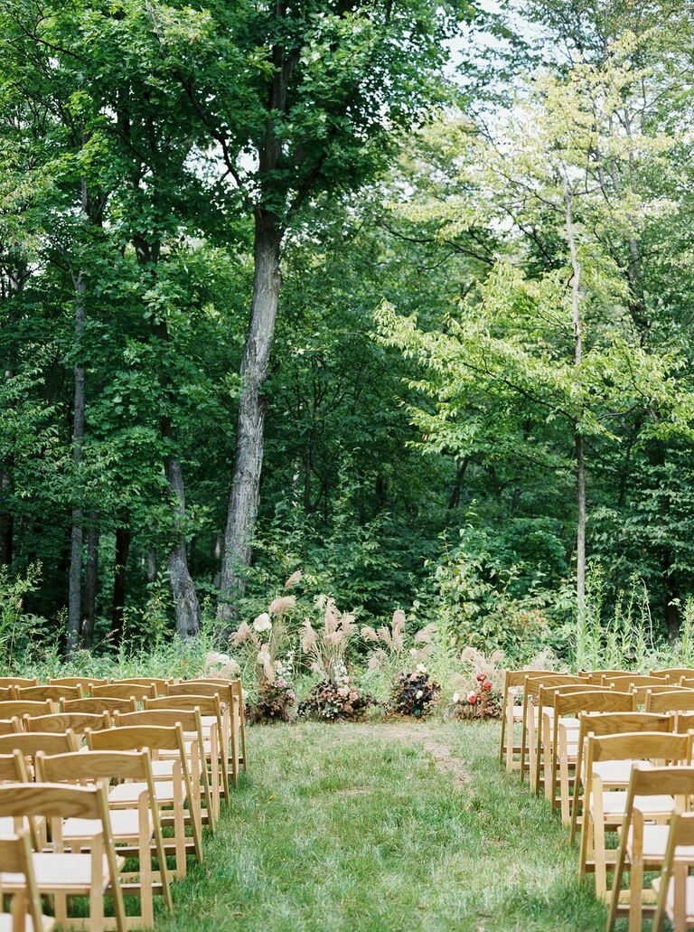 Outdoor wedding ceremony with light wood folding chairs