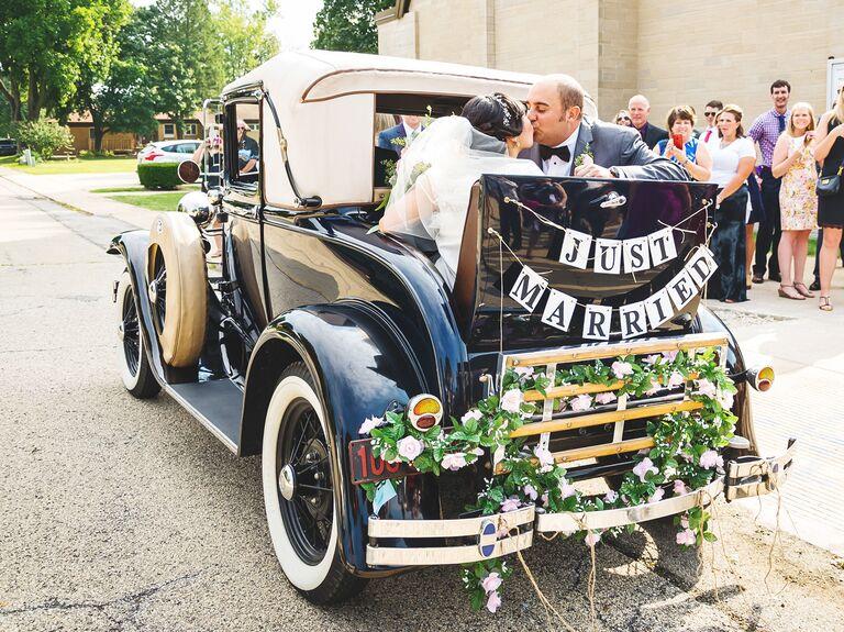 Bride and groom exiting in vintage car