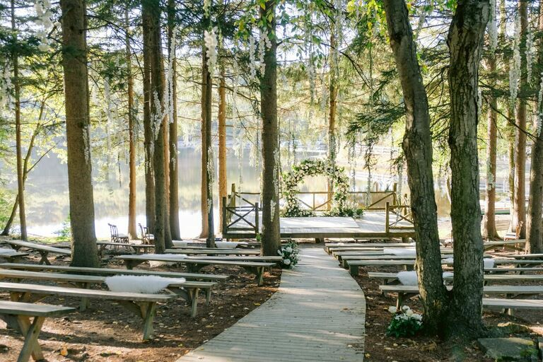 Wedding ceremony in the wood with curved aisle and floral arch