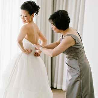 Mother zipping up wedding dress