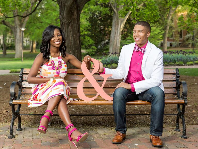 Couple sitting on bench with pink ampersand sign between them