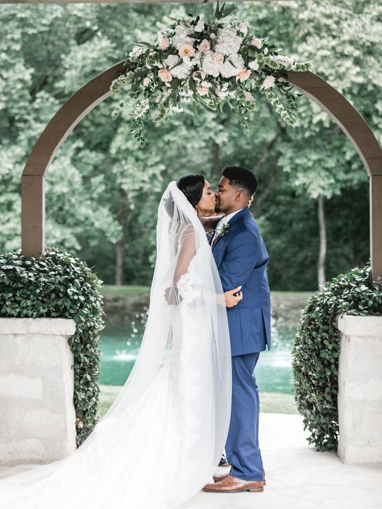 Bride and groom kiss at wedding ceremony
