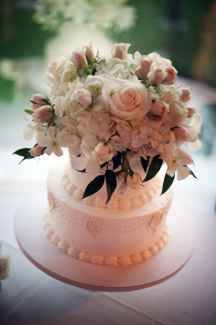 The ivory wedding cake was decorated with piping and topped off with fresh hydrangeas and roses. Inside, the cake was flavored with German chocolate and vanilla.