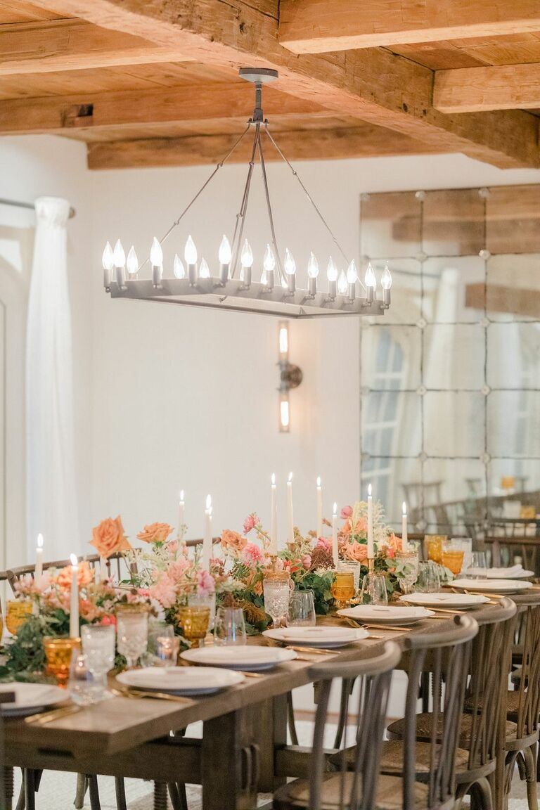 Rustic wedding reception with rectangular chandelier above farm table