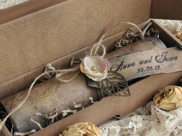 Scroll invites with vintage tag that has names and wedding date, satin flower tied around