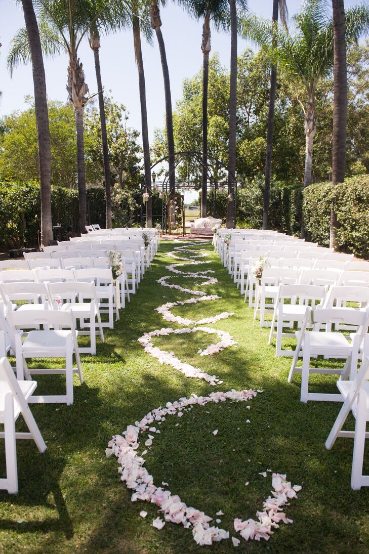 The ceremony aisle was lined with blush and white rose petals in a swirled pattern to add romance and whimsy to the outdoor ceremony site. The altar was decorated with a black iron rod arbor and a vintage couch for the couple to sit on during their traditional religious ceremony.